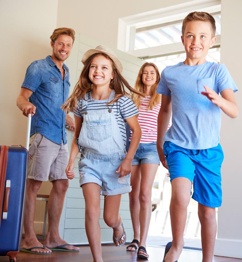 Familie kommt ins Hotelzimmer mit Koffer rein und macht Familienurlaub